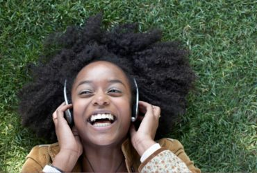 photo of a young woman listening to music while outdoors